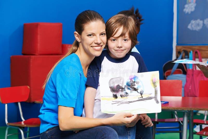 Jongen en kinderdagverblijfleraar die het schilderen tonen stock foto's