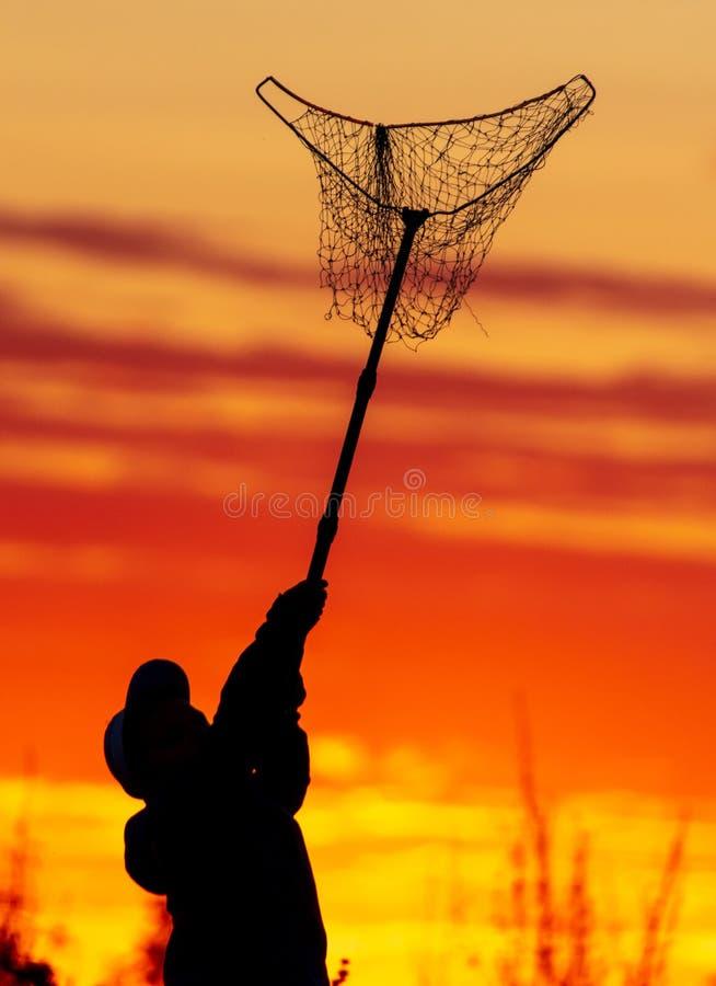 Jongen en landingsnet voor vissen op een zonsondergrond stock foto