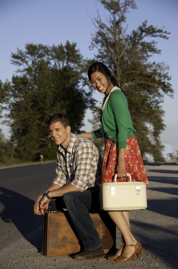 Jongen en meisje bij kant van de weg met koffer stock afbeelding