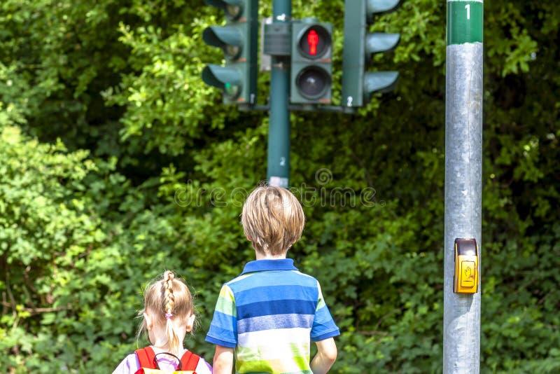 Jongen en meisje die bij het rode verkeerslicht wachten stock afbeelding