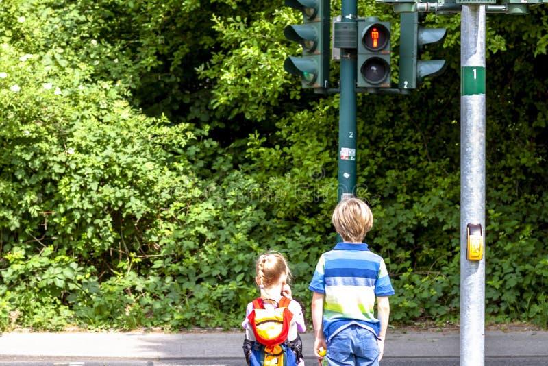 Jongen en meisje die bij het rode verkeerslicht wachten stock afbeeldingen