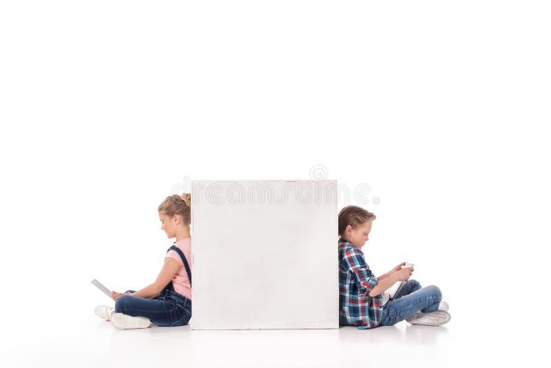 Jongen en meisje die digitale apparaten met behulp van terwijl het zitten bij witte kubus, stock foto