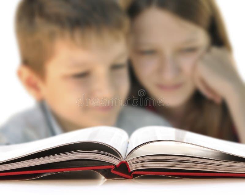 Jongen en meisje die een boek lezen royalty-vrije stock fotografie