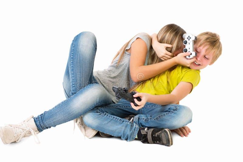 Jongen en meisje die een videospelletje en een strijd spelen stock fotografie