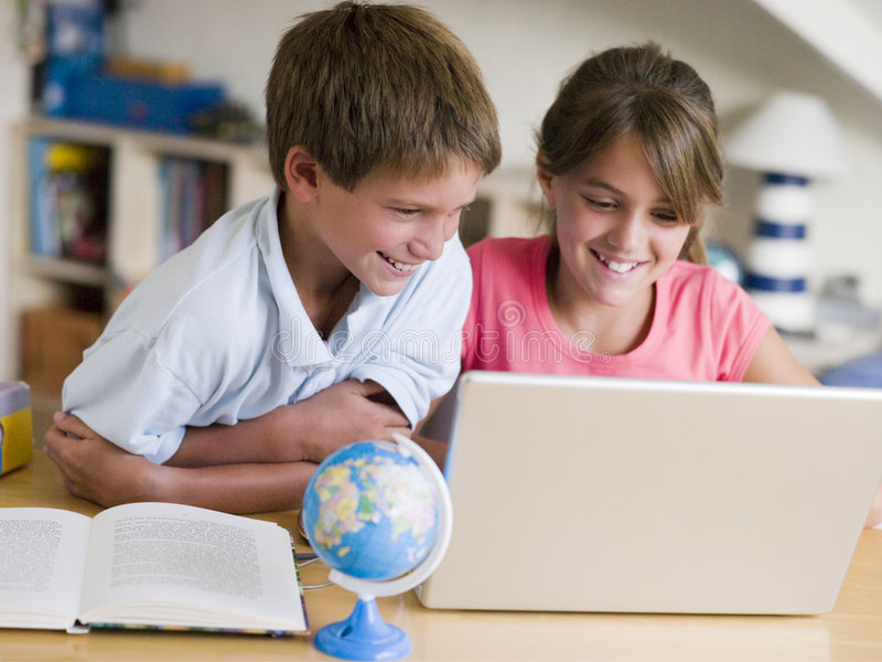Jongen en Meisje die Hun Thuiswerk op Laptop doen stock fotografie