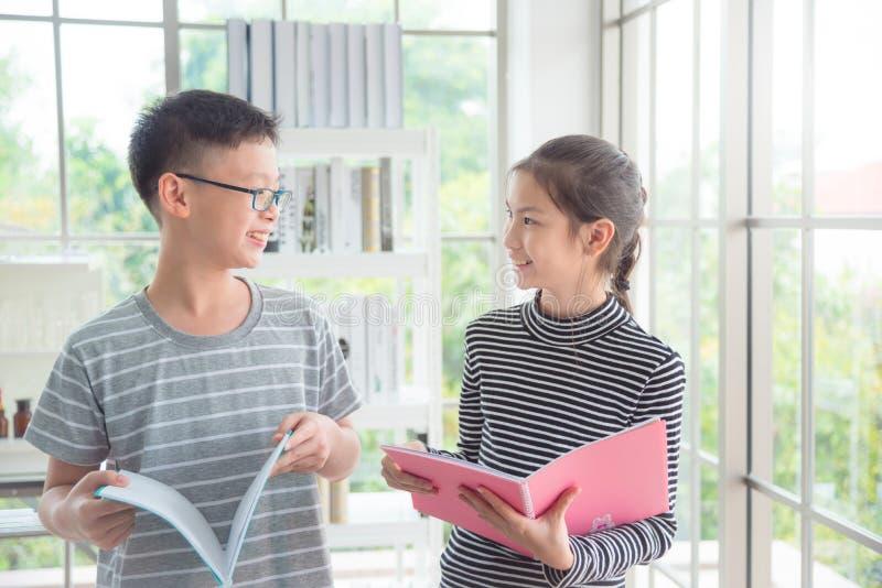 Jongen en meisje die en in klaslokaal spreken glimlachen royalty-vrije stock afbeeldingen