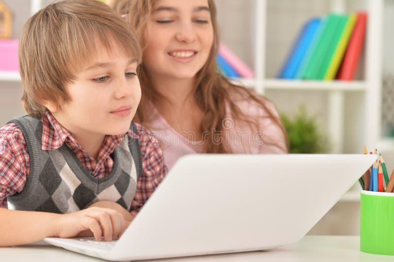 Jongen en meisje die laptop samen thuis met behulp van royalty-vrije stock afbeeldingen