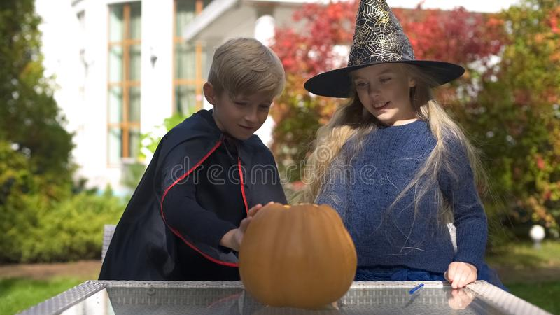 Jongen en meisje die in maskeradekostuums eng gezicht op pompoen, Halloween trekken stock afbeeldingen