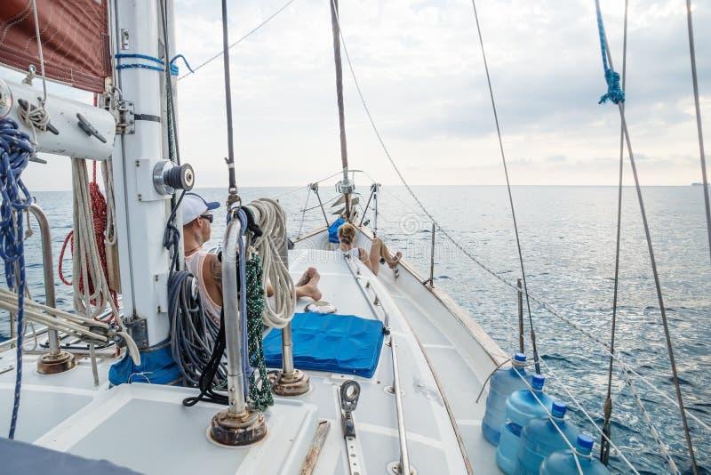 Jongen en meisje die op dek voor een zeilboot in Caraïbische Zee dichtbij Utila, Honduras, Midden-Amerika liggen stock afbeelding