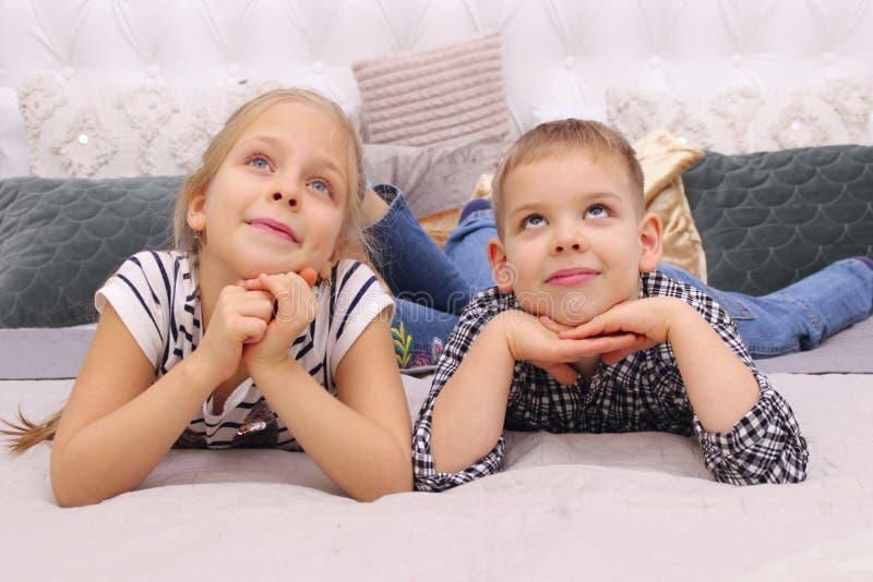 Jongen en Meisje die op een Bed liggen De oudere Broer Dreaming van Zusterand her younger stock foto