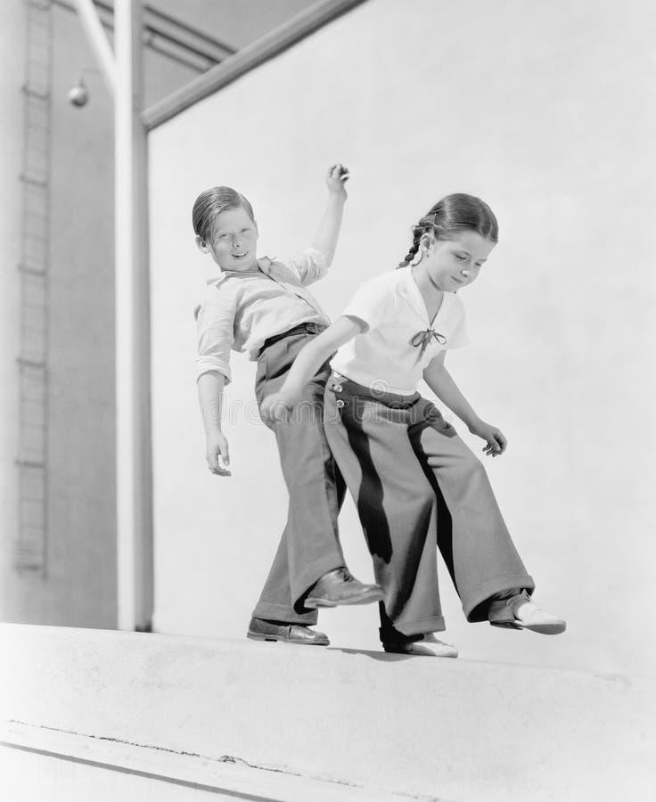 Jongen en meisje die op een richel proberen in evenwicht te brengen (Alle afgeschilderde personen leven niet langer en geen landg royalty-vrije stock foto's