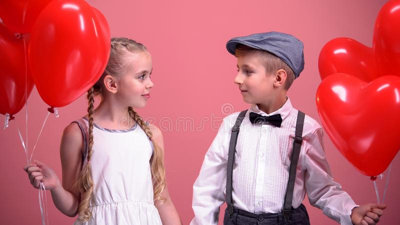 Jongen en meisje die rode hartballons houden en elkaar, eerste liefde bekijken royalty-vrije stock afbeelding