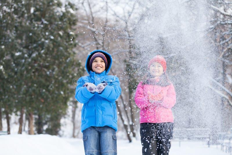 Jongen en meisje die sneeuw werpen in lucht stock fotografie