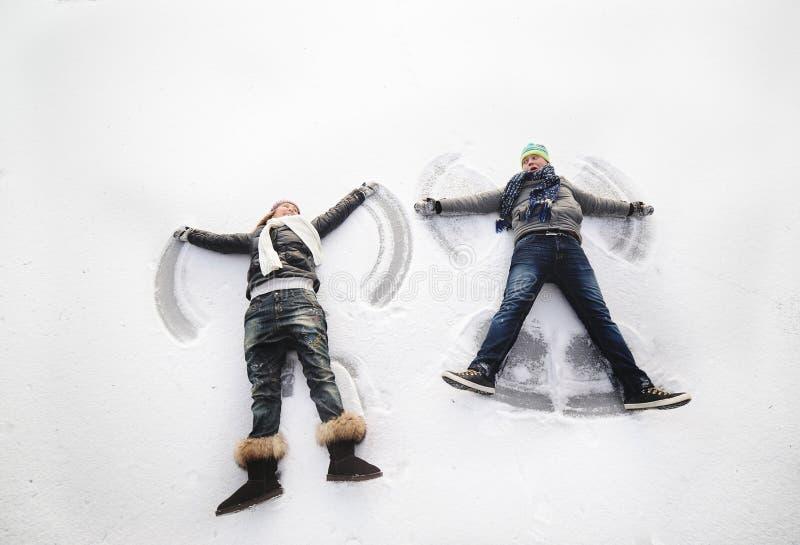 Jongen en meisje die sneeuwengelen maken stock foto