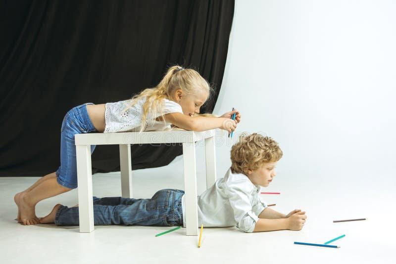 Jongen en meisje die voor school na een lange de zomeronderbreking voorbereidingen treffen Terug naar School stock foto