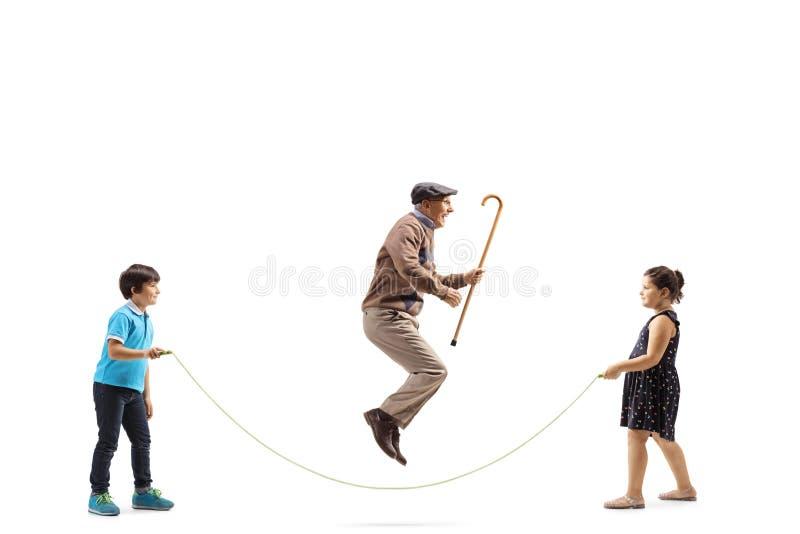 Jongen en meisje een kabel houden en een hogere mens die met riet het springen royalty-vrije stock fotografie