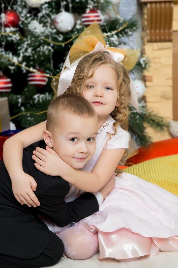 Jongen en meisje met giften dichtbij de Kerstboom stock afbeelding