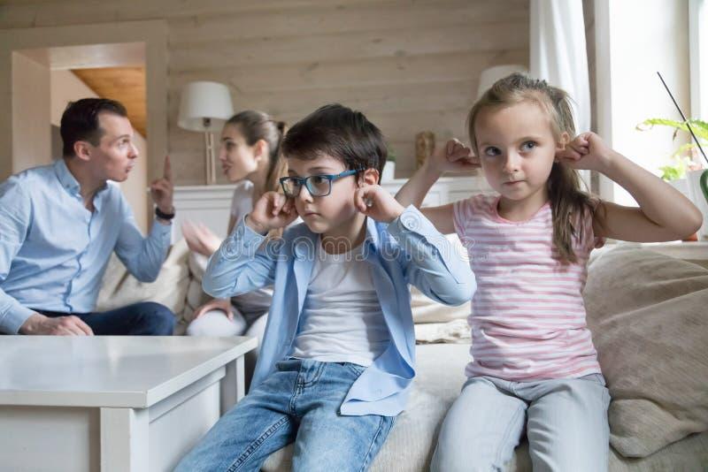 Jongen en meisjes dichte oren om ouders het ruzie maken niet te horen royalty-vrije stock foto's