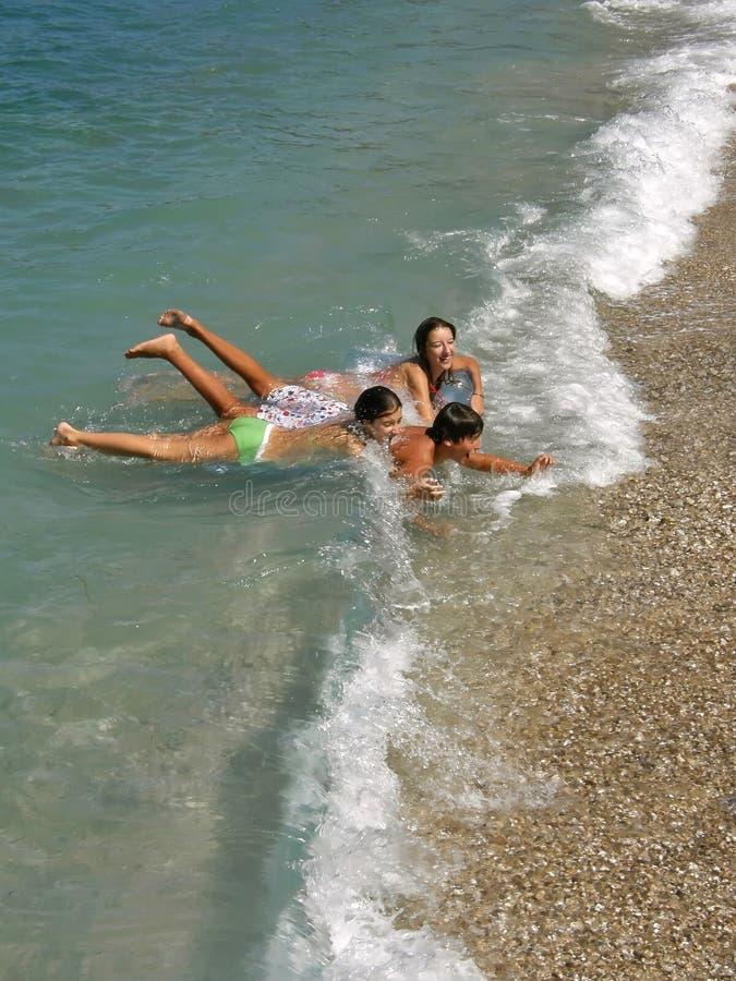 Jongen en meisjes die op golven spelen stock afbeelding