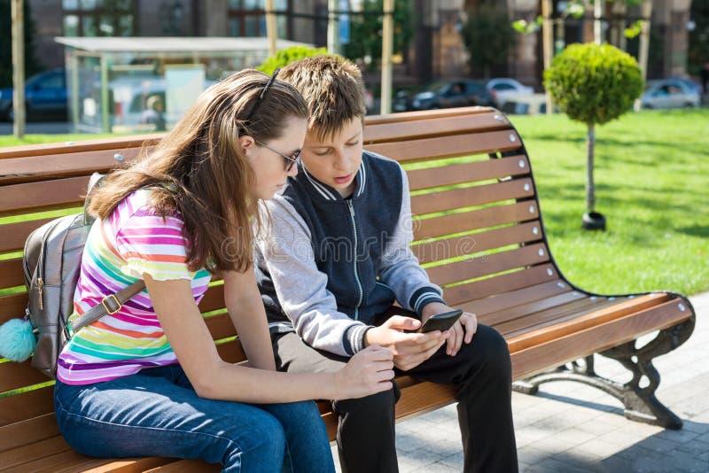Jongen en meisjes het gelezen tienersspel, bekijkt smartphone Voor de bank, de stedelijke achtergrond stock foto