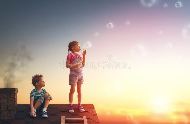 Jongen en meisjes het spelen op het dak stock fotografie