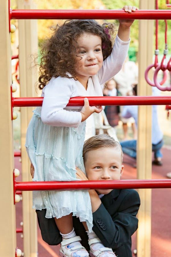 Jongen en meisjes het spelen in speelplaats stock foto