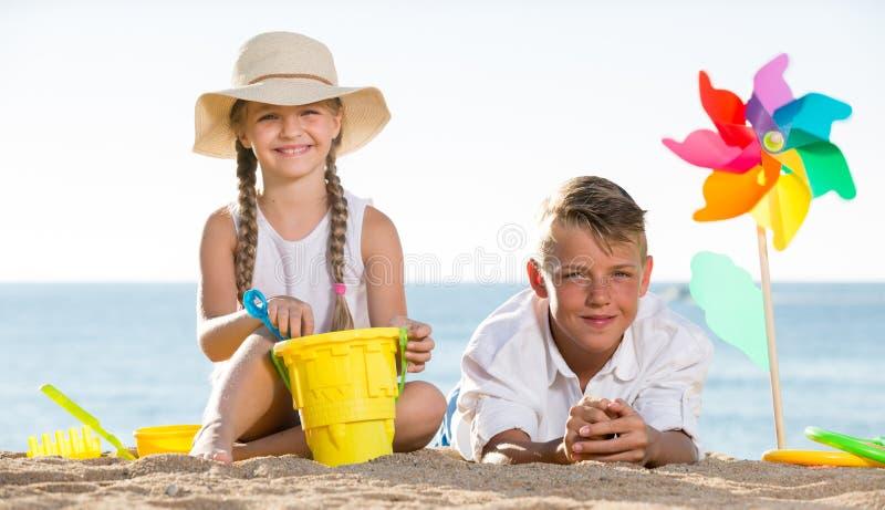 Jongen en meisjes het spelen strand stock afbeelding
