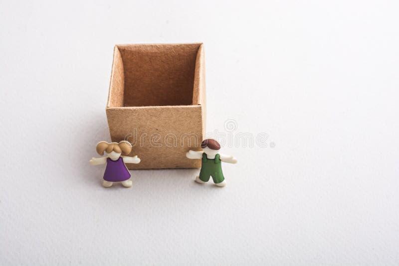 Jongen en meisjesbeeldje naast een lege doos stock fotografie