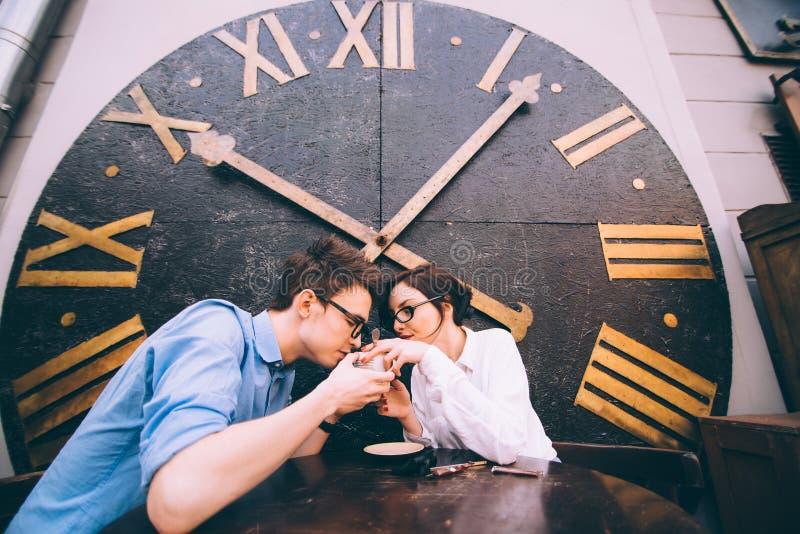 Jongen en meisjeszitting bij een lijst in een koffie stock afbeelding