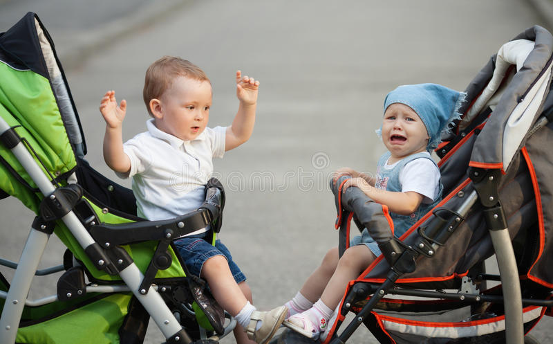 Jongen en meisjeszitting in kinderwagens stock afbeelding