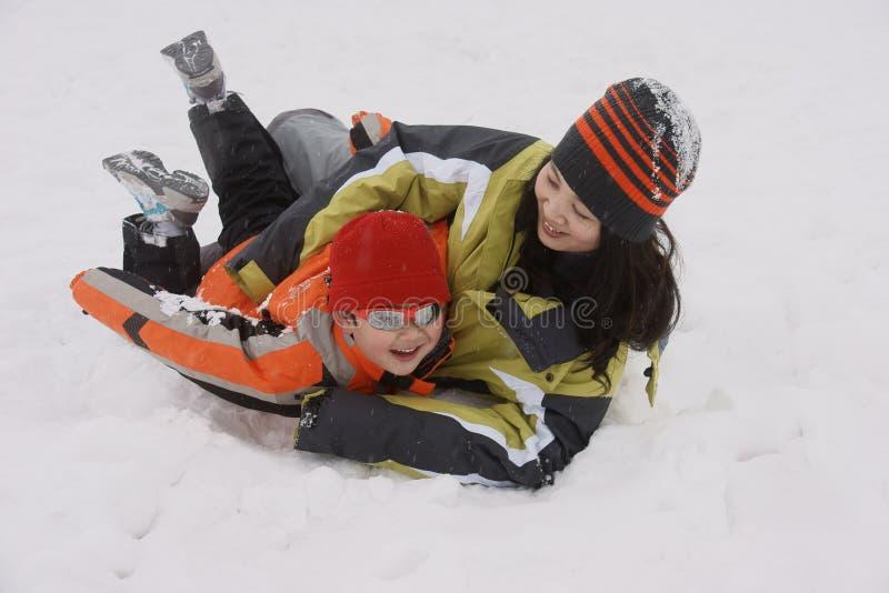 Jongen en moeder die grote pret in sneeuw hebben stock afbeeldingen