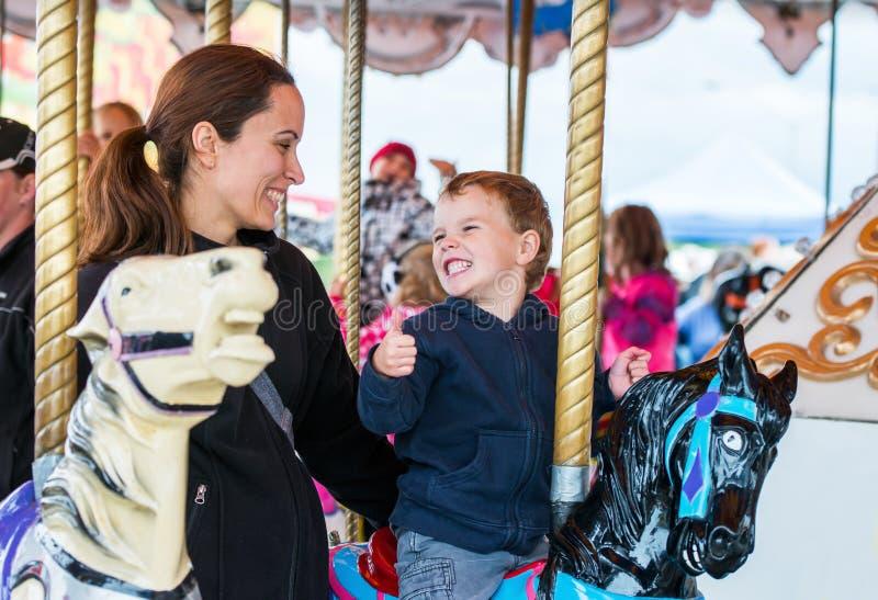 Jongen en Moeder die op Carrousel bij elkaar glimlachen stock foto's