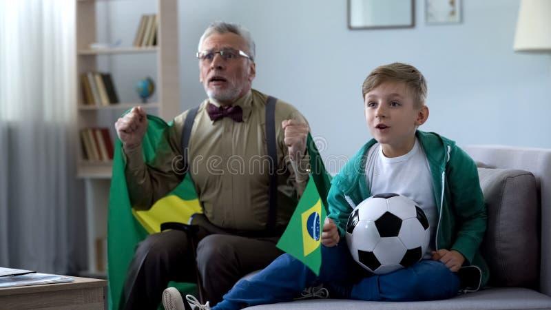 Jongen en opa de vlaggen van holdingsbrazilië, het letten op voetbal, die zich over spel ongerust maken royalty-vrije stock fotografie