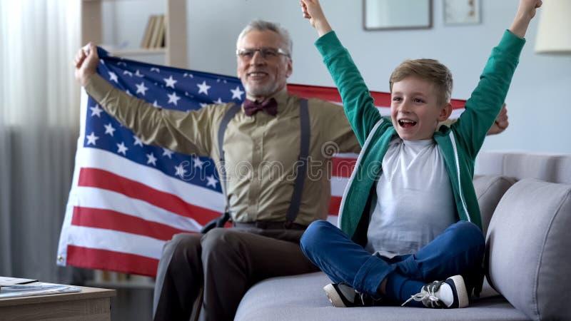 Jongen en opa die Amerikaanse vlag golven, lettend sport op spel thuis, gelukkig voor winst royalty-vrije stock fotografie