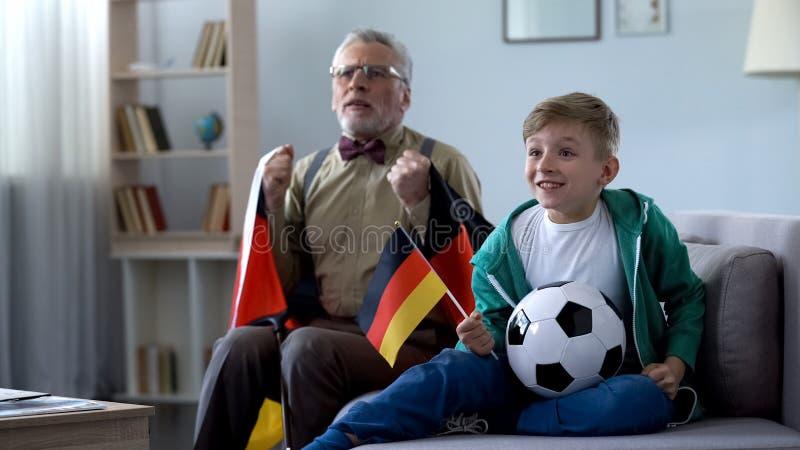 Jongen en opa die Duitse vlaggen houden, lettend op voetbal, die zich over spel ongerust maken stock foto