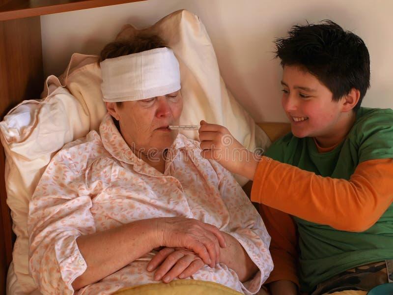 Jongen en zieke oude dame stock afbeelding