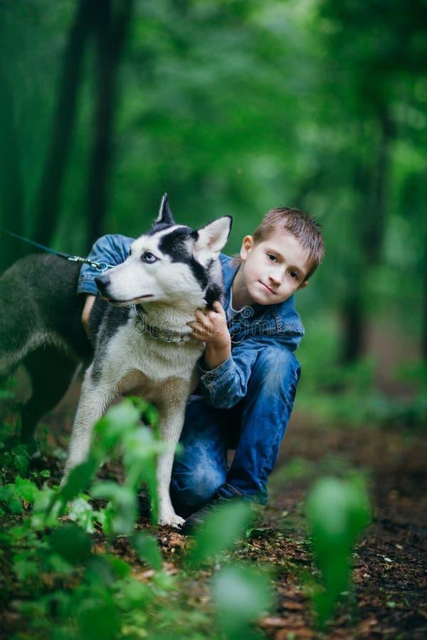Jongen en zijn hond schor op de achtergrond van bladeren in de lente royalty-vrije stock afbeelding