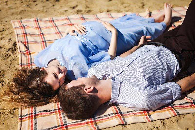 Jongen en zwanger meisje die op zand rusten royalty-vrije stock afbeelding