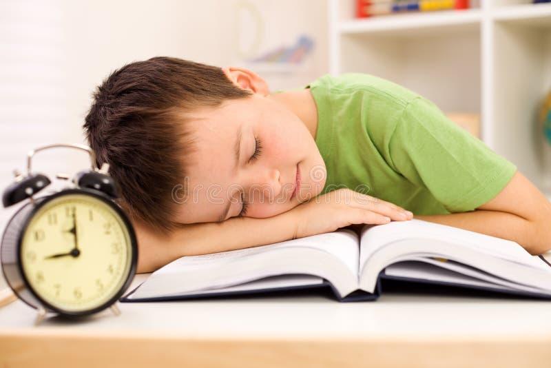Jongen gevallen in slaap op zijn boek terwijl het bestuderen royalty-vrije stock afbeeldingen