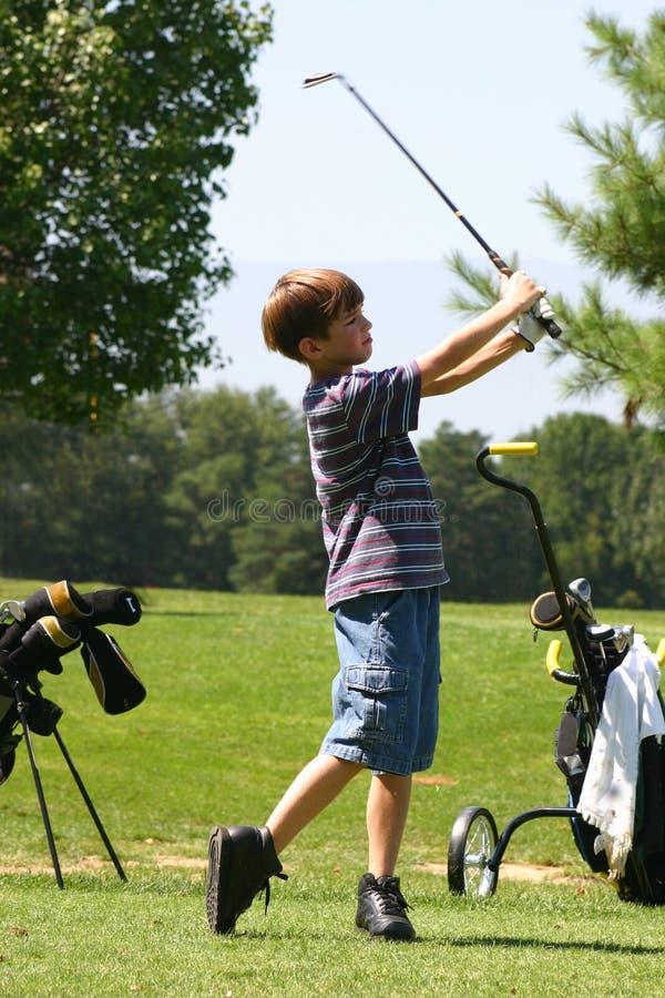Jongen Golfing stock foto's
