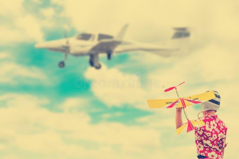 Jongen in het Breien van hoeden die met een stuk speelgoed vliegtuig spelen royalty-vrije stock afbeeldingen