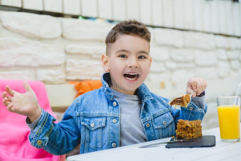 Jongen het drinken sap en het eten van pastei voor gezond ontbijt in toevluchtkoffie openlucht stock afbeeldingen