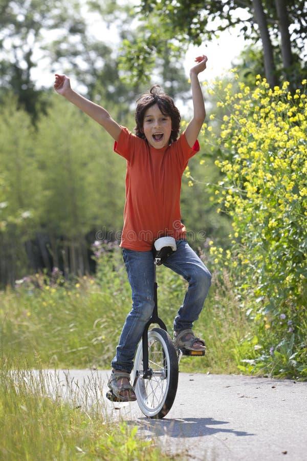 Jongen het in evenwicht brengen op een unicycle stock foto