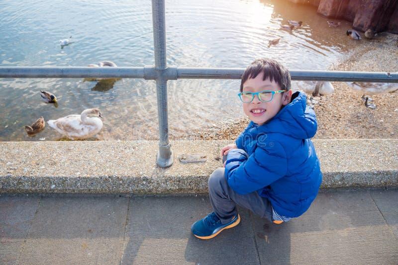 Jongen het letten op eenden en zwanen in de rivier stock fotografie