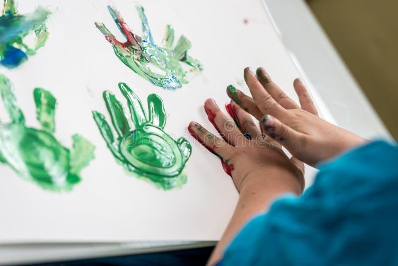Jongen het schilderen met zijn handen die kleurrijke palmdrukken maken royalty-vrije stock fotografie