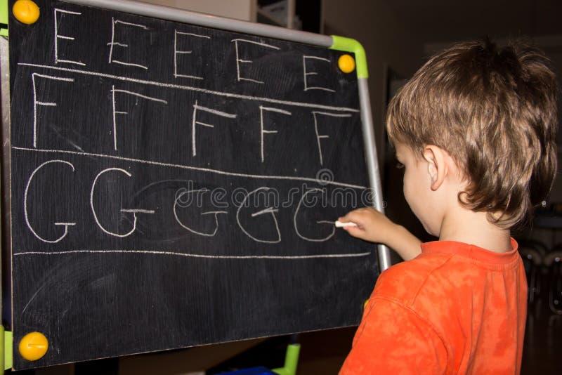 Jongen het schrijven de kennis van het brieven leerproces van klein kind stock foto's