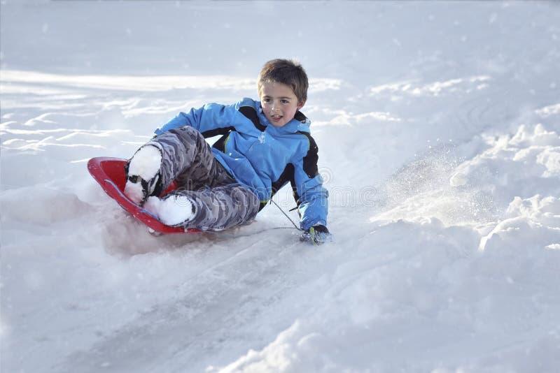Jongen het sledding onderaan een heuvel in de sneeuw stock fotografie