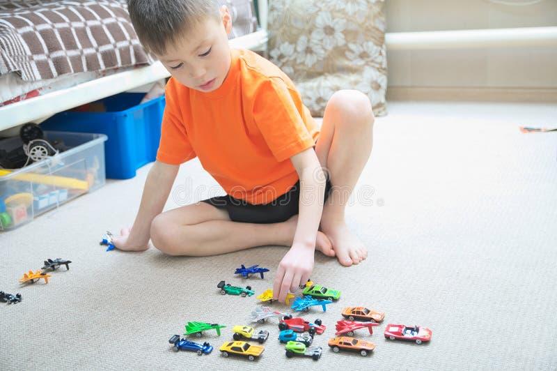 Jongen het spelen met autoinzameling op tapijt Het huis van het kindspel Vervoer, vliegtuig, vliegtuig en helikopterspeelgoed voo royalty-vrije stock fotografie