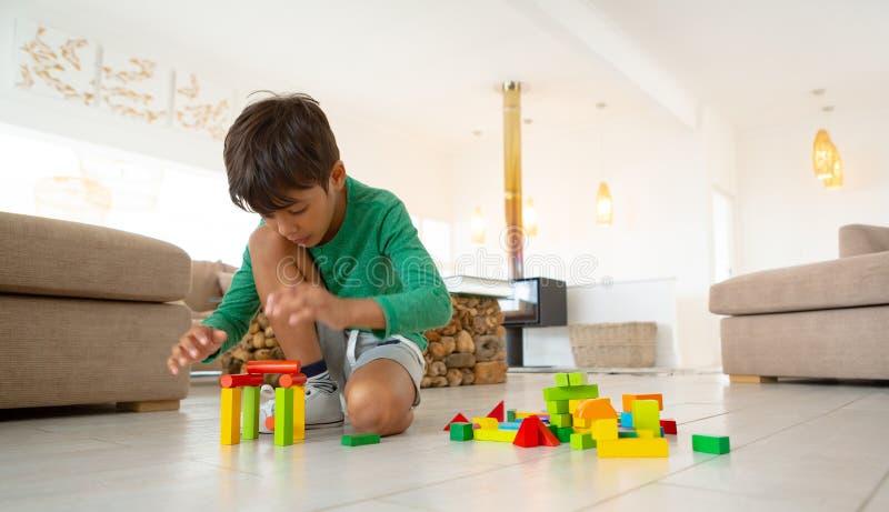 Jongen het spelen met bouwstenen op vloer in woonkamer bij comfortabel huis stock afbeelding