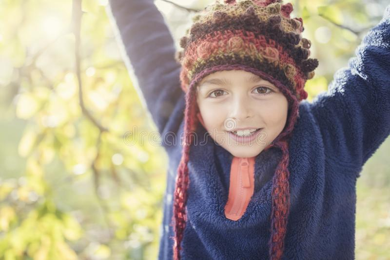 Jongen het spelen met de herfstbladeren in het park royalty-vrije stock afbeeldingen